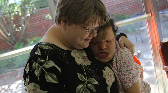 Brandi Davis, 29, hugs Amanda Holland as the two play games at the adult day care at the Oklahoma Foundation for the Disabled in Oklahoma City. Holland, 27, suffers from cardiofaciocutaneous, a rare genetic disorder.