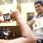 Eight-year-old Ann George takes a photo of her father, George Varghese, a new citizen from India, during a June 24 naturalization ceremony at the federal courthouse in Oklahoma City.