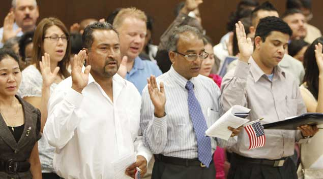 Former Mexican citizen Ernesto Rosas (left) and former Indian citizens Simon Mascarenhas and George Varghese take the oath of citizenship during a June 24 naturalization ceremony at the federal courthouse in Oklahoma City.