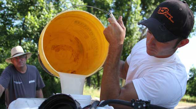 Chad Selman, operator of S & S Pecans, pours a zinc mixture into a sprayer machine on the back of his all-terrain vehicle as his father and company owner, Chuck Selman, waits. The Selmans do most of the work on their farm during the summer and hire temporary visa workers, usually from Mexico, during the fall to help with harvesting pecans.