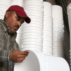 Luis Carlos Aguirre Piña, of Chihuahua, Mexico, cleans buckets that will be used to store organic wheat. He works at an organic wheat farm and cattle ranch in Fairview. He is in the U.S. on an H-2A temporary agricultural work visa.