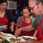 Taco Shop proprietor Jose Perez prepares a dish as Gaby Perez and Pati Ramos look on.