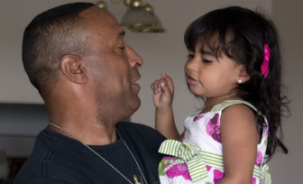 "Stephen Leon, a combat veteran who is now 70 percent disabled, holds his granddaughter Ashley A. De Leon at his apartment in Revere, Mass. in June. Leon said that before he found an independent advocate he didn't think anyone at the VA would give him a ""dime"" for claims."