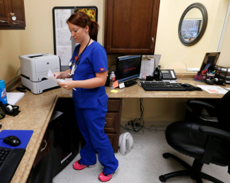 X-Ray tech Jessica Dossey works in the reception area at Rockford Medical Access Clinic, a walk-in clinic operated by St. John Medical Center in Tulsa.