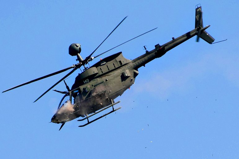 An OH-58 Kiowa helicopter fires its .50 caliber machine gun during a strafing run on an enemy compound during a live-fire exercise in January 2012 at Fort Polk, La.