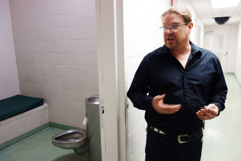 Clint Womeldorff, assistant superintendent of the Tulsa County Juvenile Detention Center, stands in front of a holding cell, equipped with cameras, for residents experiencing trauma. The center is moving to comply with federal rape protection standards.